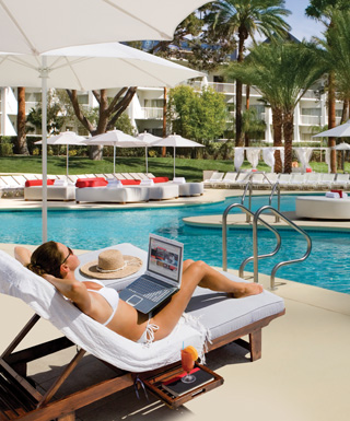 woman laying by trop pool with laptop in her lap